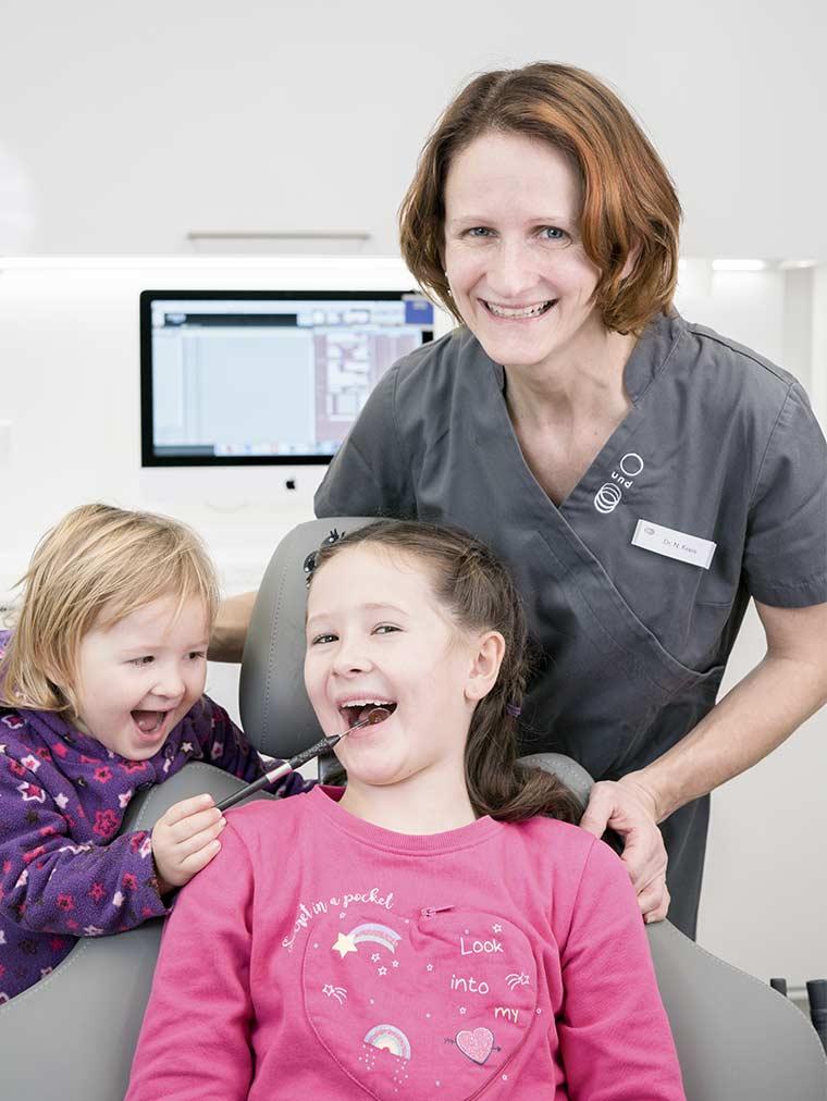 Kinderzahnaerztin Dr. Nadine Kreis mit zwei Kindern am Behandlungsstuhl